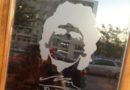 Author appears in a reflection of a window etched with Maradona's face and signature.
