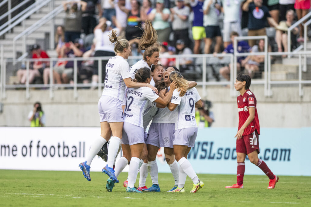 Racing players leap on Yuki Nagasato who is screaming in the air after her incredible goal