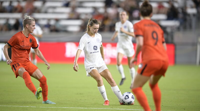 Emina Ekic of Racing Louisville passes the ball with Houston players waiting in the foreground