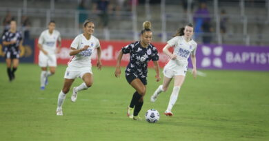 Ebony Salmon of Racing Louisville makes a run past Rose Lavelle and another Reign player