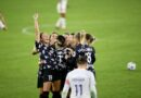 Racing Louisville players celebrate Yuki Nagasato's goal clustered together on the pitch. Taylor Otto raises her fist and cheers to the left side of the group.